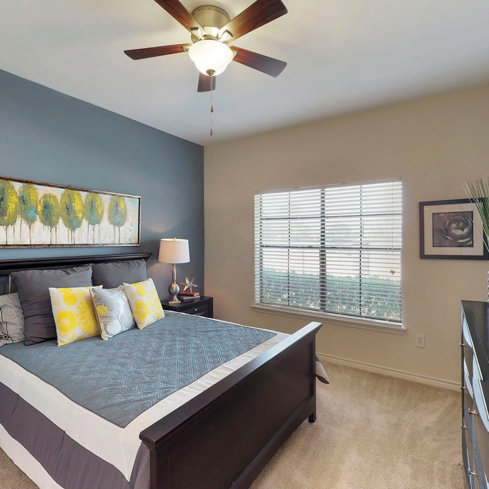 Accent wall and bay windows in a model apartment's primary bedroom at Oaks Riverchase in Coppell, Texas