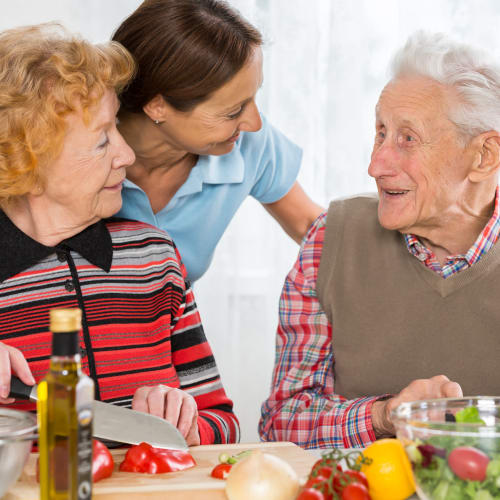 A Caretaker from At Home Care Group in Oregon assisting a couple make dinner in their home.