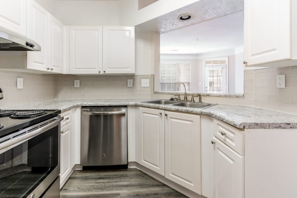 Bright kitchen with wood flooring and stainless steel appliances at Marquis at Sugarloaf in Duluth, Georgia