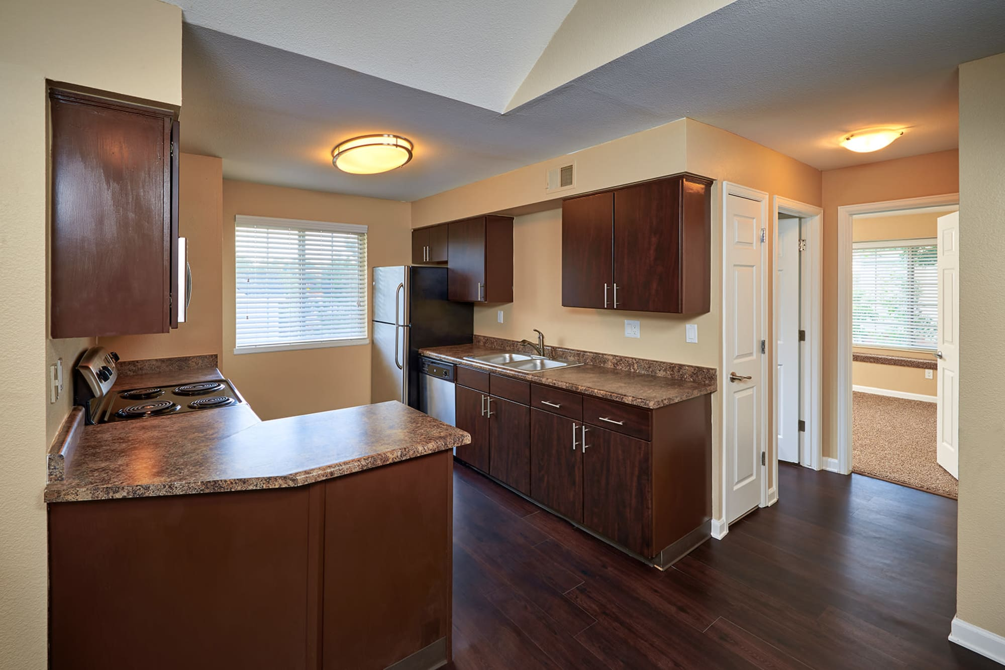 kitchens with brown cabinets at Villas at Homestead Apartments