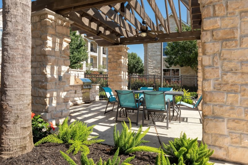 Barbecue area with gas grills overlooking the swimming pool at The Retreat at Cinco Ranch in Katy, Texas