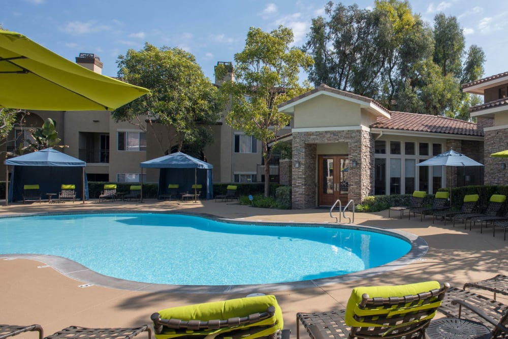 Swimming pool with a large sundeck and plenty of lounge chairs at Alize at Aliso Viejo Apartment Homes in Aliso Viejo, California