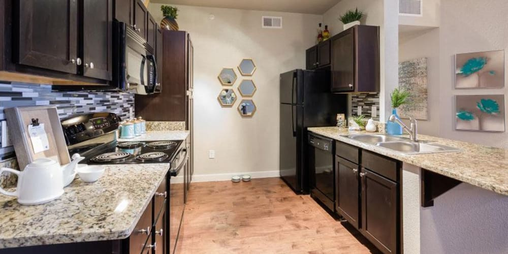 Dark wood cabinets and ample counter space in the kitchen at Verandas at Alamo Ranch in San Antonio, Texas