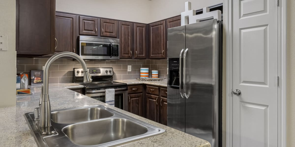 Modern kitchen with granite counters and stainless steel appliances at Marquis at Kingwood in Kingwood, Texas