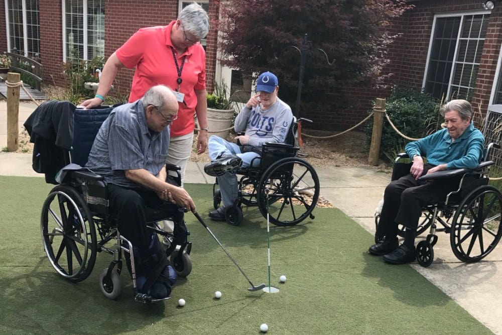 A group of residents playing mini golf with assistance from a caretaker at Springhurst Health Campus in Greenfield, Indiana