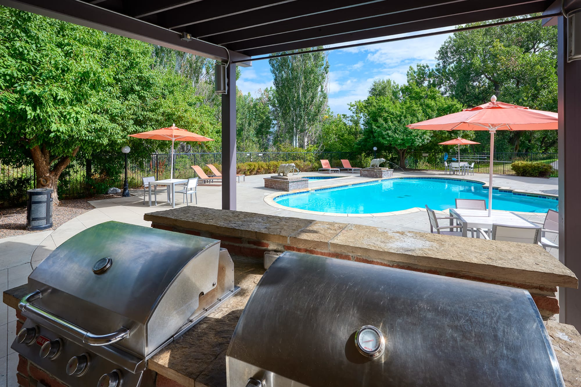 The poolside covered outdoor BBQs at The Crossings at Bear Creek Apartments in Lakewood, Colorado