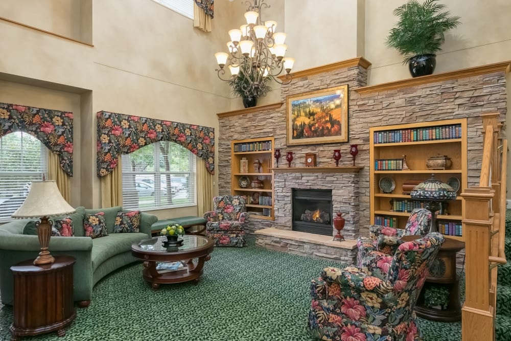 Fireplace and seating area with a staircase at Applewood Pointe Woodbury in Woodbury, Minnesota.