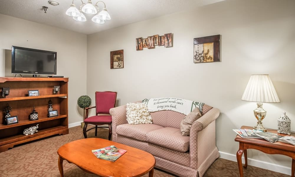 Resident activity room with books, couch, and TV at Randall Residence of Tiffin in Tiffin, Ohio