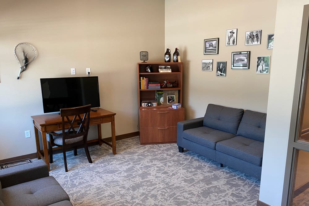 Sitting area with modern couches and TV at Country Meadow Place in Mason City, Iowa