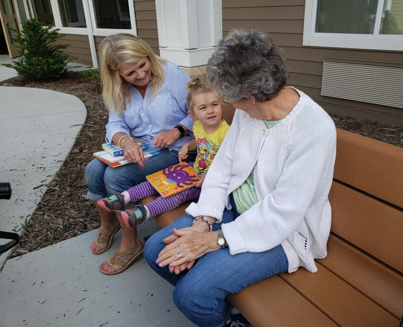 A young child and resident sit together on a bench at Arbor Glen Senior Living in Lake Elmo, Minnesota