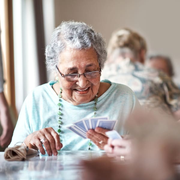 Woman playing cards at The Crest at Citrus Heights in Citrus Heights, California