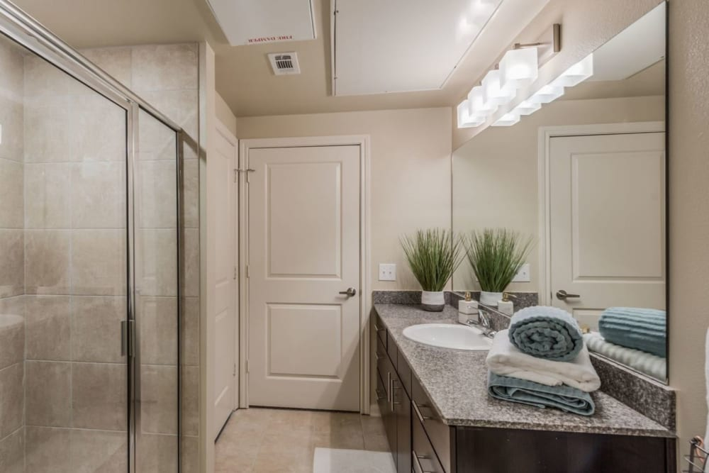 Model bathroom with oversized vanity and tiled shower enclosure at Heights West 11th in Houston, Texas