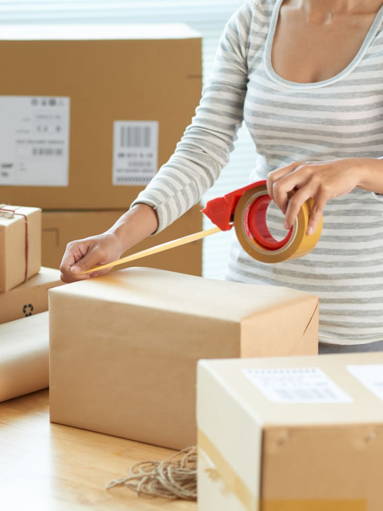 A lady packing a moving box at Store It All Self Storage in San Antonio, Texas