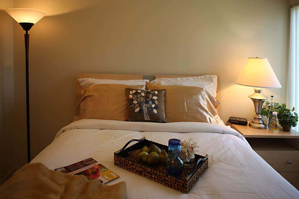 Well-decorated bed in bedroom of model home at Kensington Manor Apartments in Farmington, Michigan