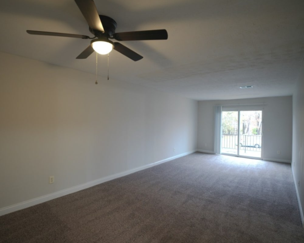 A living room with a ceiling fan at Tanglewood Apartments in Louisville, Kentucky