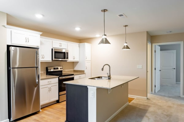 Kitchen with stainless-steel appliances at Bennington Hills Apartments in West Henrietta, New York
