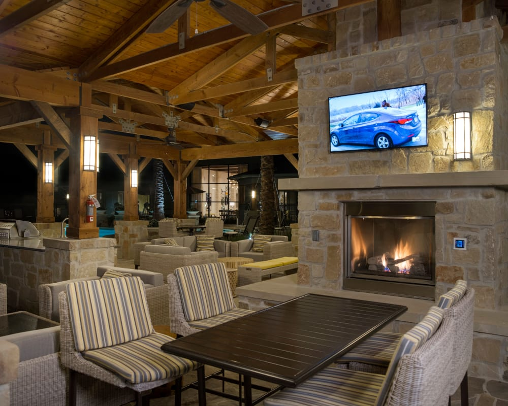 Covered outdoor seating with a fireplace and TV at Savannah Oaks in San Antonio, Texas.