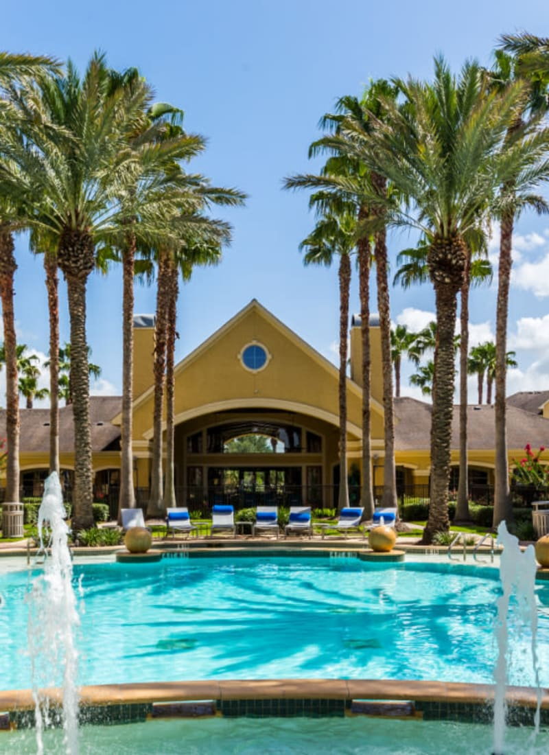 Sparkling resort style pool with water features and lounge chairs at Marquis at Clear Lake in Webster, Texas