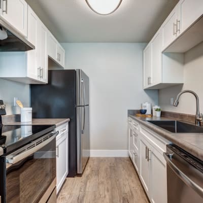 Modern kitchen with bright white appliances and cabinetry in a model home at Sofi Union City in Union City, California