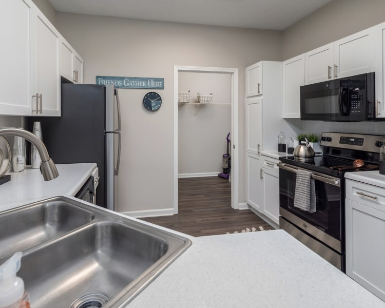 Model apartment's kitchen with stainless-steel appliances and white cabinetry at Highlands at Alexander Pointe in Charlotte, North Carolina