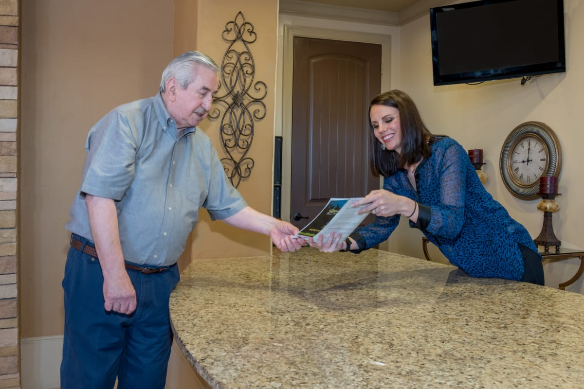 A resident requesting a brochure at the front desk at Watercrest at Bryan in Bryan, Texas