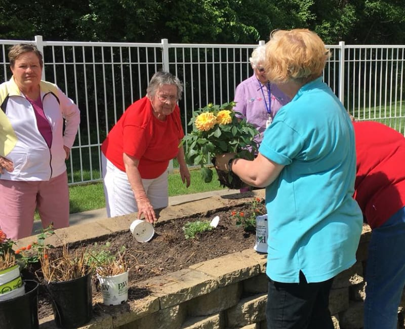 Residents planting flowers outside at Deer Crest Senior Living in Red Wing, Minnesota
