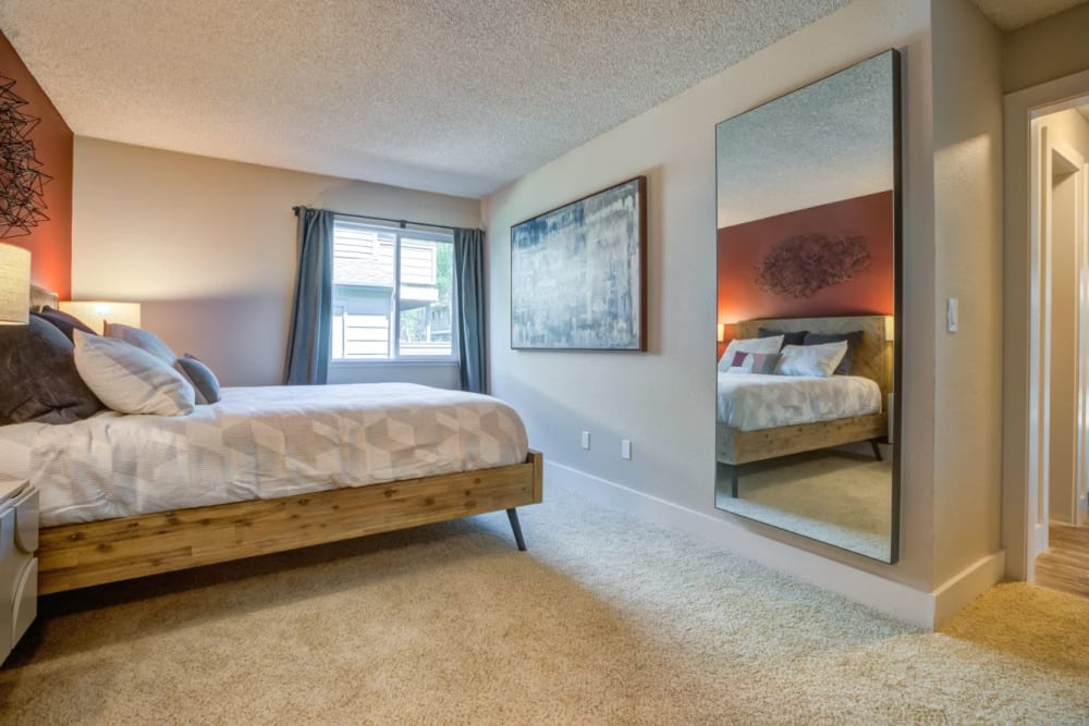 Plush carpeting and a draped window in a model home's bedroom at Sofi Union City in Union City, California