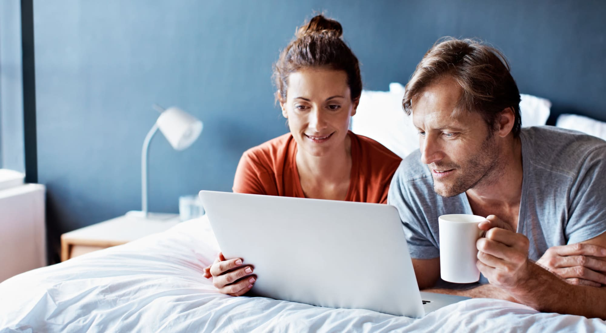 Young couple laying in bed using a laptop at Fusion apartments in Jacksonville, Florida