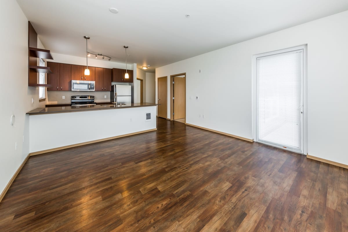 Living room and kitchen with wood style flooring at Marq West Seattle in Seattle, Washington