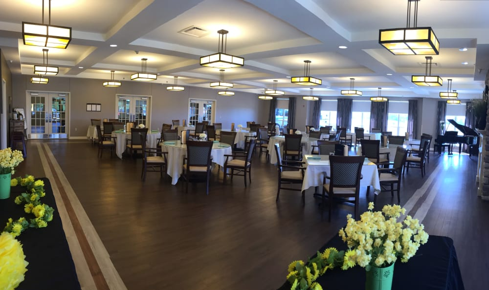 Dining room with a grand piano at Arcadia Senior Living Bowling Green