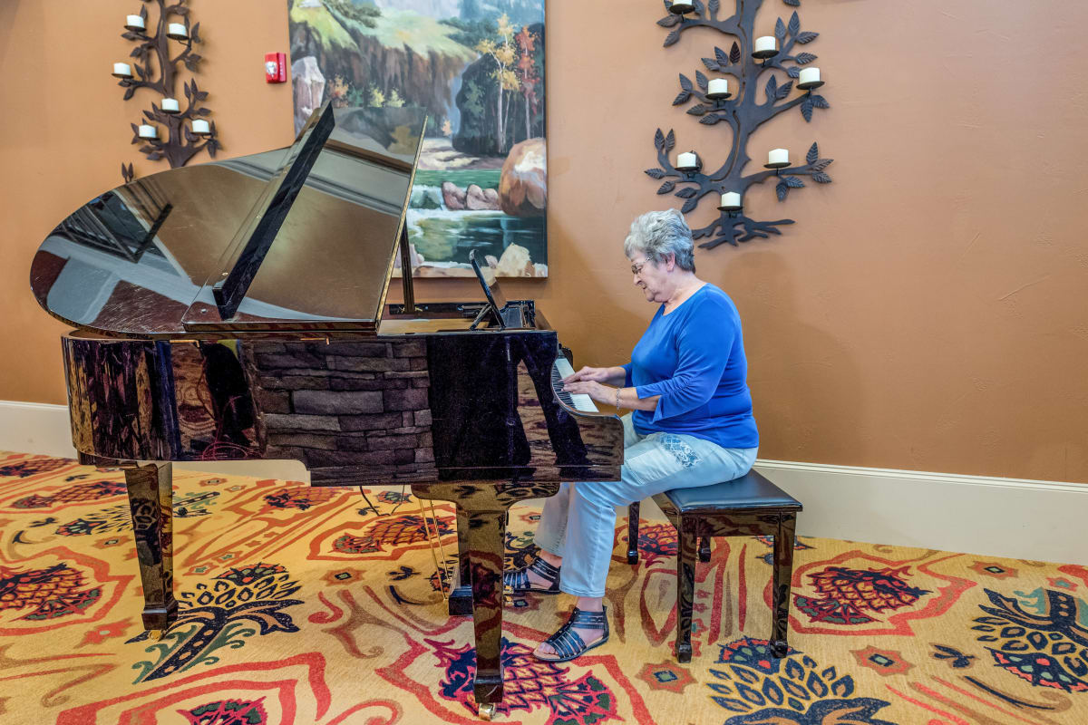 Resident playing piano at Raider Ranch in Lubbock, Texas