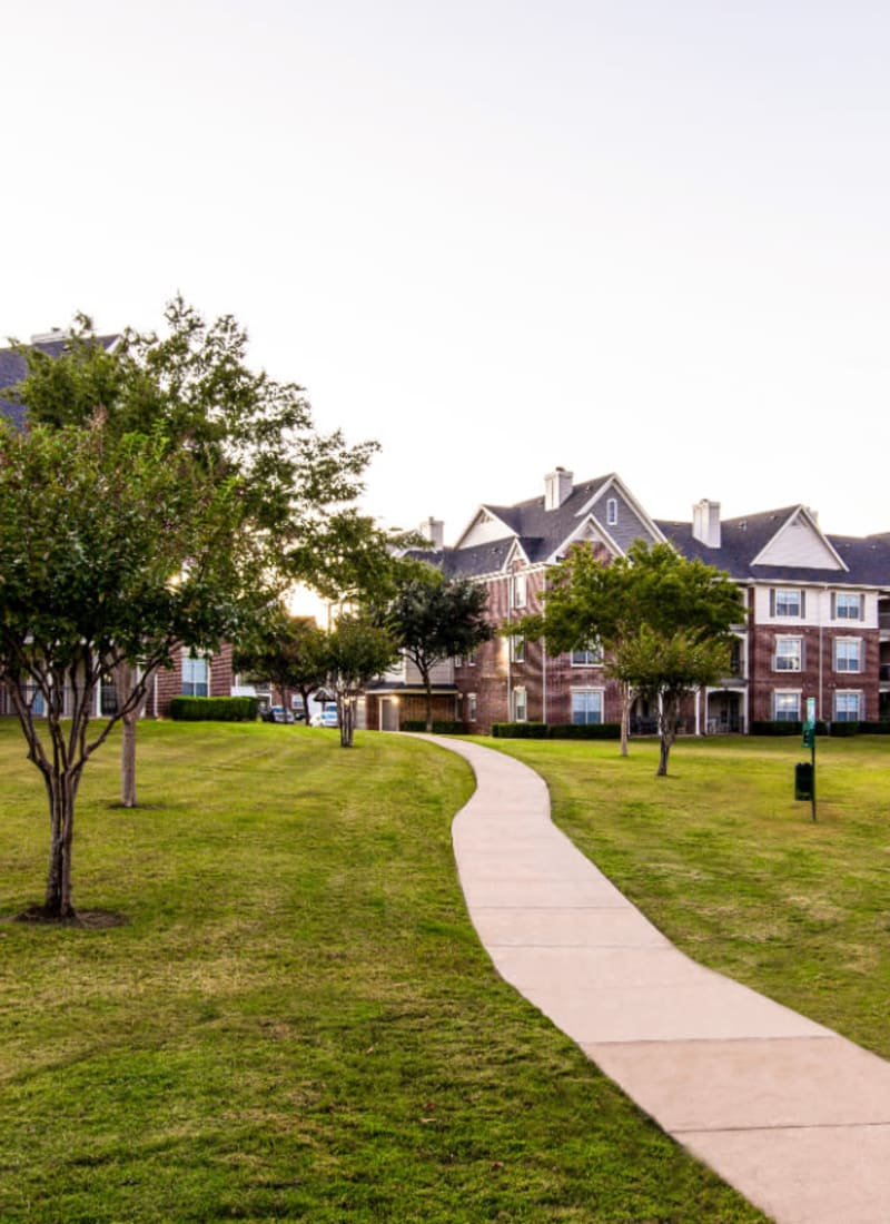 Walking path through unit buildings with dog waste station at Marquis at Silver Oaks in Grapevine, Texas