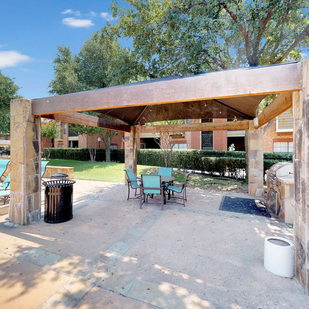 Covered barbecue area with gas grills at Oaks Riverchase in Coppell, Texas