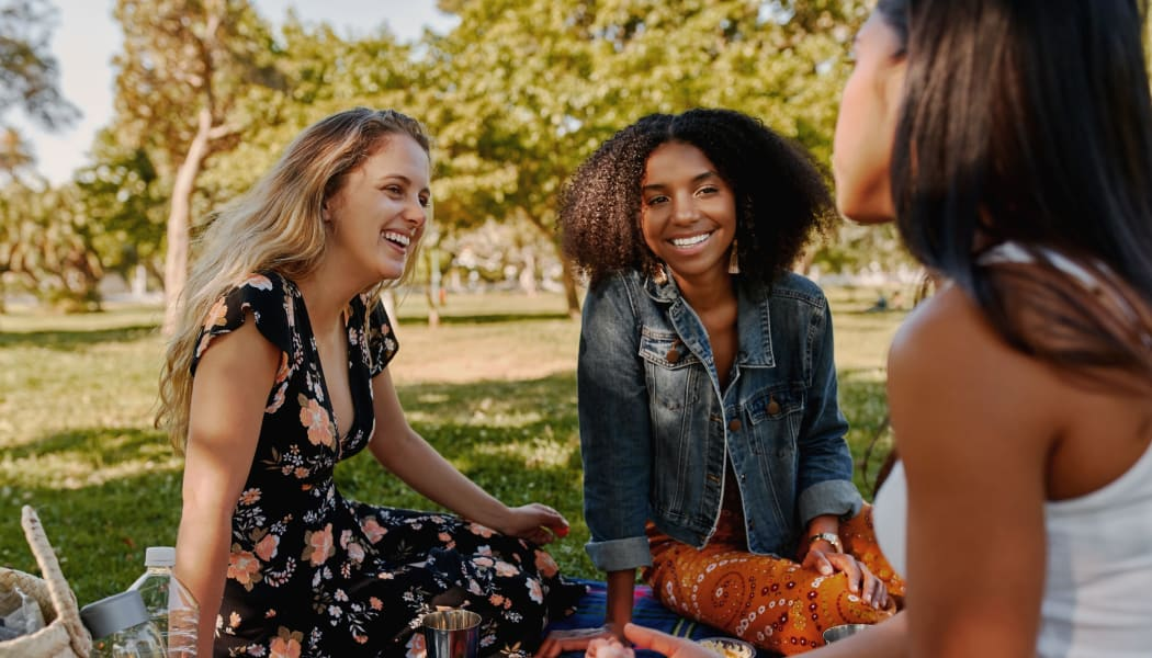 Friends enjoying a picnic at a local park in Lubbock, Texas near Cottages at Abbey Glen Apartments