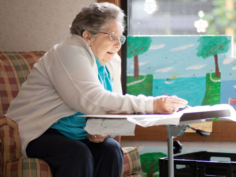 Resident painting in the sunlight at Villa at the Lake in Conneaut, Ohio