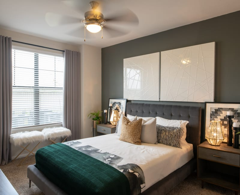 Main bedroom with large windows and ceiling fan at Haven at Liberty Hills in Houston, TX