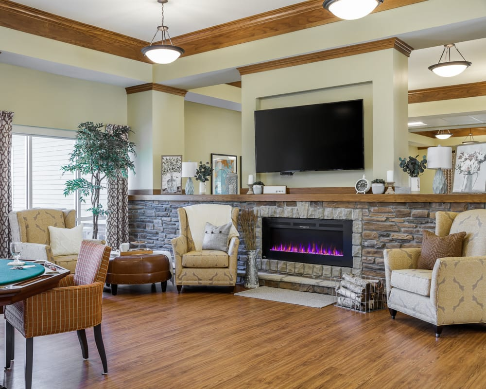 Lounge with a big tv, game tables, and a fireplace at Edencrest at The Legacy in Norwalk, Iowa.