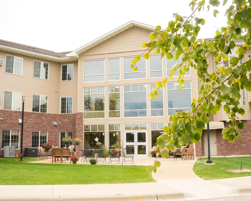 Rear entrance and courtyard with park benches at Prairie Meadows Senior Living in Kasson, Minnesota.