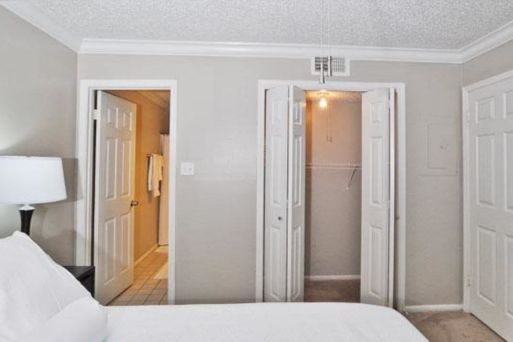 Comfy bed and closet at French Colony Apartments in Lafayette, Louisiana