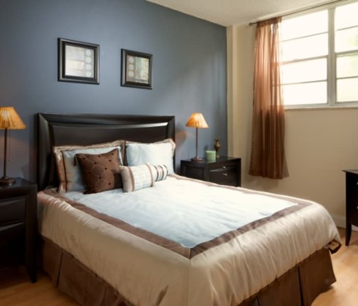 Bedroom with accent wall in model home at Aliro Apartments in North Miami, FL