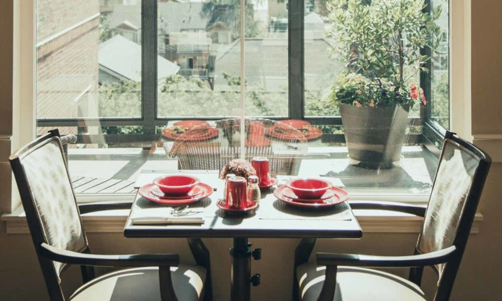 Dining table for 2 by a window at Quail Park Memory Care Residences of West Seattle in Seattle, Washington