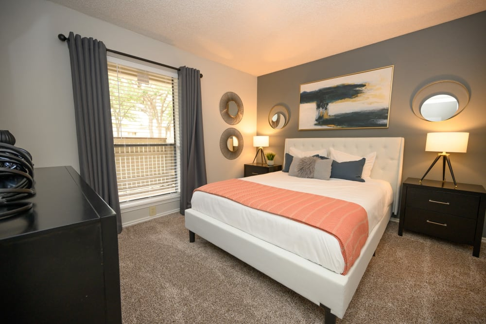 Furnished bedroom with large window to get lots of natural light at The Logan in Bedford, Texas