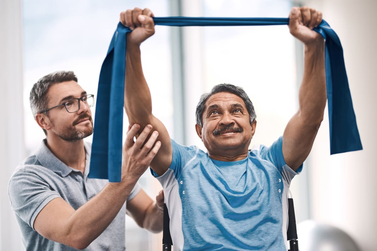 Resident Using stretch bands with assistant supporting arms