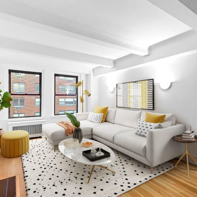 Spacious living room with a large panel windows at The Sutton Collection in New York, New York