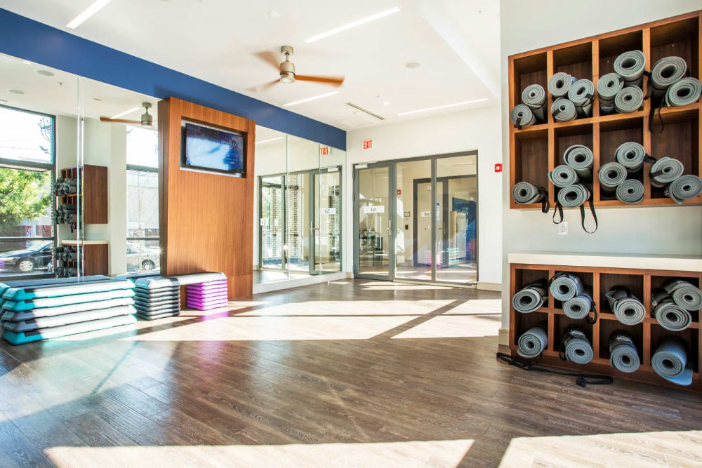 Rack with stored rolled up yoga mats in open fitness area at Marq Midtown 205 in Charlotte, North Carolina