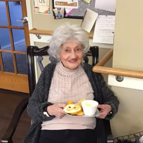 A resident seated with a breakfast plate in her hand at Canoe Brook Assisted Living & Memory Care in Catoosa, Oklahoma