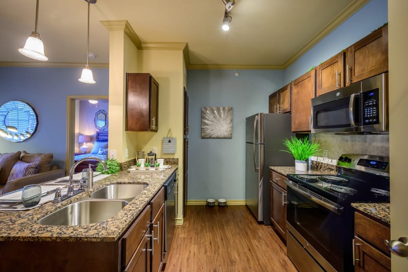 View of kitchen with hardwood floors at Pecan Springs Apartments in San Antonio, Texas