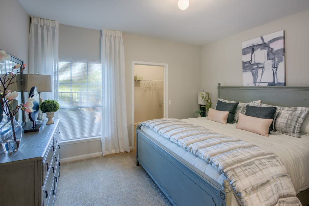 Well lit model bedroom with carpeted floors at The Vive in Kannapolis, North Carolina