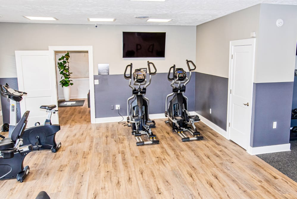 A fitness center with spin bikes and a flat-screen TV at Silver Lake Hills in Fenton, Michigan