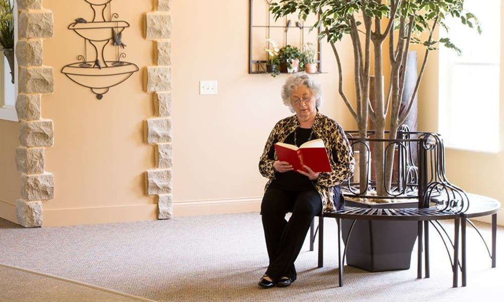 Resident reading a book in a common area at Randall Residence of Tipp City in Tipp City, Ohio